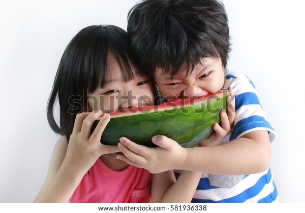 Cute little Asian boy and girl enjoying watermelon isolated on white background