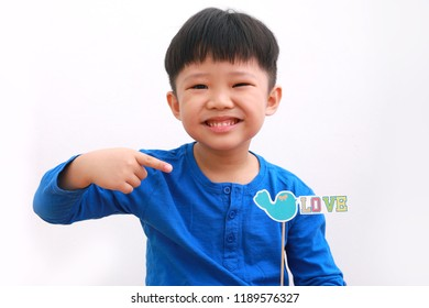 Cute little asian boy holding a photo-booth prop of twitter bird love, with funny expression, isolated on white background.