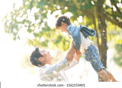 cute little asian boy lifted by father outdoors in park