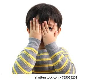 Cute little Asian boy peeks through his fingers, isolated on white background