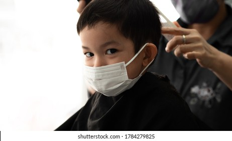 Cute little Asian boy  with protective mask and barber man or parent with protective mask doing a hair cut in the quarantine at home Covid-19
