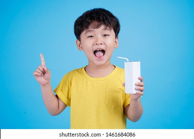 Cute little asian child boy hold milk box and drink on white background isolated