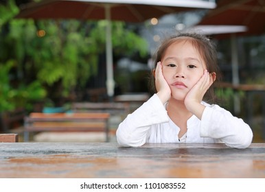 Cute little Asian child girl expressed displeasure on the wood table