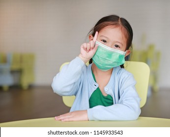 Cute little Asian child girl wearing a protective mask with showing one forefinger sitting on kid chair in children room.