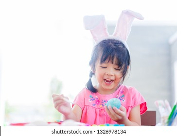 Cute little asian child girl wearing bunny ears on Easter day.Little asian Girl painting  easter egg in Church on Sunday morning in Easter day.Easter day is Jesus Risen and Alive.