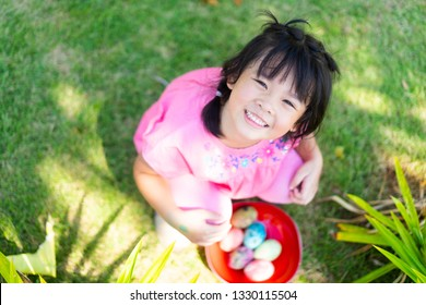 Cute little asian child girl hunt easter egg on Sunday morning at Church in Easter day.Happy Girl holding red basket with painted eggs and seek for easter egg.Easter day is Jesus Risen and Alive.