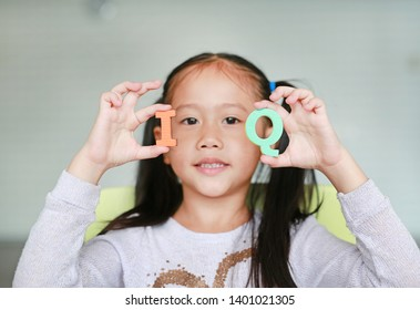Cute little Asian child girl holding alphabet IQ (Intelligence Quotient) text on her face. Education concept.