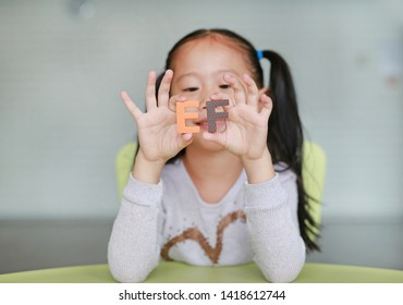 Cute little Asian child girl holding alphabet EF (Executive Functions) text on her face. Education and development concept.