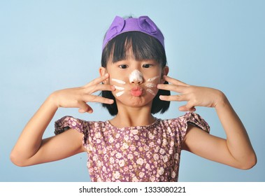 Cute little asian girl with a cat costume plays on blue background.