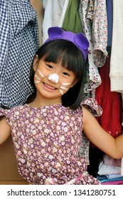 Cute little asian girl with a cat costume plays in her wardrobe.