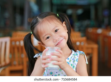 Cute Little asian girl drinking glass of fresh milk in coffee shop.