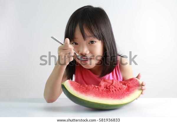 Cute little Asian girl enjoying watermelon isolated on white background
