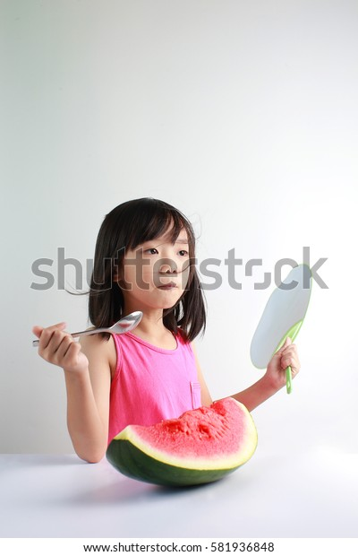 Cute little Asian girl enjoying watermelon with a fan during summer isolated on white background