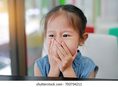 Cute Little asian girl hold the hands over her mouth.