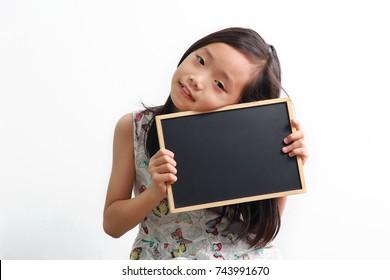 Cute little Asian girl holding a blank chalk board