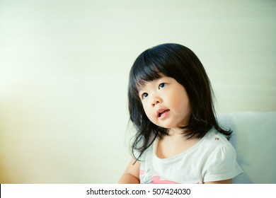 Cute little asian girl looking and talk to her mother.