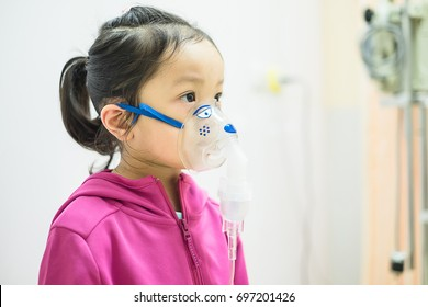 Cute little asian girl making inhalation with a nebulizer mask in the hospital. Kid allergy concept
