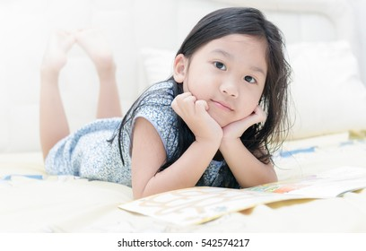 Cute little asian girl in nightdress reading a book and smiling while lying on bed in the bedroom. education concept