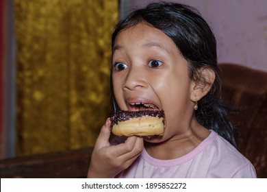 Cute little asian girl is opening her mouth wide to eat a donut.