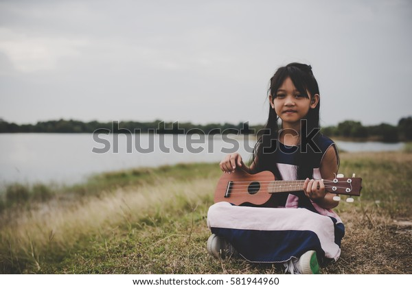 Cute little asian girl sitting on grass and play ukulele in park.