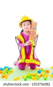 Cute little Asian girl wearing yellow hard hat and yellow reflective safety vest, role-playing building constructor show her completed toy building made of multi-color blocks toy bricks and blocks