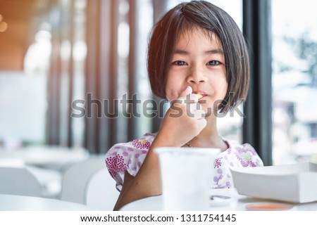 0b6ee09e2f91 A cute little asian kid eating fried chicken at home. She enjoys yummy meal  as