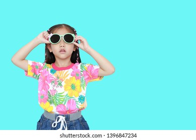 6894f37919f1 Cute little Asian kid girl wearing a flowers summer dress and sunglasses  isolated on cyan background
