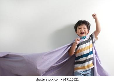 Cute little Asian kid superhero on white background.