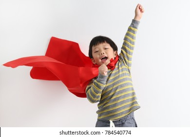 Cute little Asian superhero kid on white background. Boy power concept.