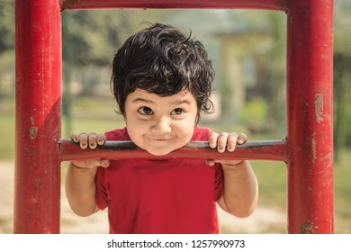 Cute little Asian/Indian child making funny faces, playing at kid play ground looking at camera and climbing up iron ladder.