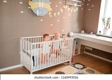 Cute little babies looking out of the bed in the room