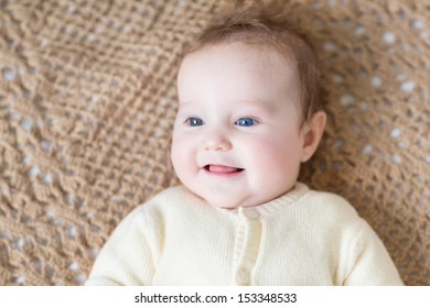 Cute little baby with beautiful blue eyes wearing a warm sweater playing on a brown knitted blanket