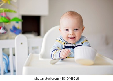 Cute little baby boy, eating mashed vegetables for lunch, mom feeding him, sweet toddler boy, smiling