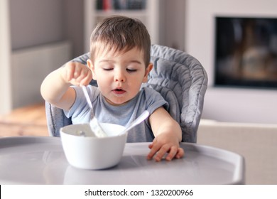 Cute little baby boy with funny smeared face concentrated on food eating with fork from white bowl at table in front of him sitting in high feeding chair. Attempt to eat by himself. Child nutrition