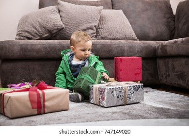 Cute little baby boy in green jacket playing with colorful wrapped gifts in a living room