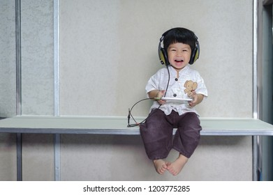 cute little Baby Boy holding in hands the smartphone ,enjoying watching and listening Music form smart phone