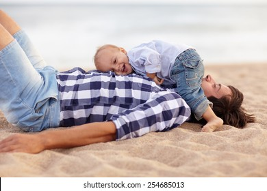 Cute little baby boy lying on his dad's chest and laughing out loud at the beach