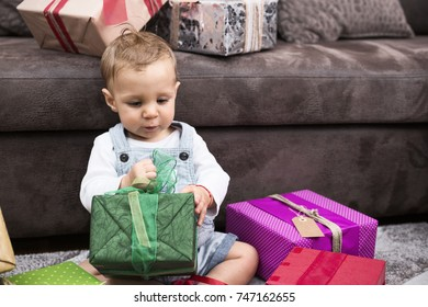 Cute little baby boy plays with gifts in a living room