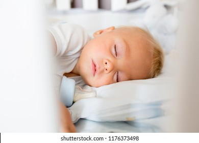 Cute little baby boy, sleeping with bottle with formula milk. Tired child in baby cot bed