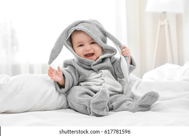 Cute little baby in bunny costume sitting on bed at home