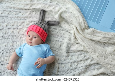 Cute little baby in bunny hat lying on soft blanket