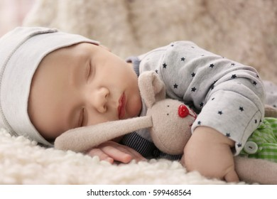 Cute little baby with bunny toy sleeping on plaid at home, closeup