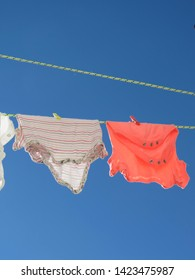 Cute Little Baby Clothes Hanging on the Clothesline against the Blue Sky