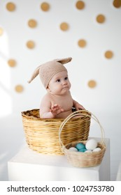 Cute little baby dressed as a bunny on Easter day sitting in a wicker basket