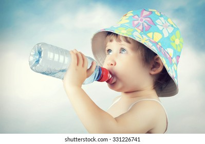 A cute little baby is drinking water from a bottle