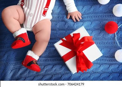 Cute little baby with gift box and garland on knitted fabric