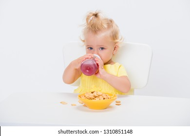 Cute little baby girl 1 year old eating cereal flakes and drinking juice or compote from a bottle at the table isolated on white background.