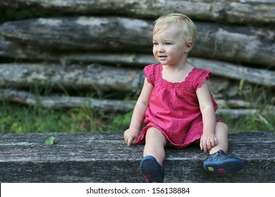 Cute little baby girl in beautiful red dress relaxing after walk in a forest sitting on a wooden bench