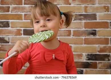 Cute little baby girl with big green lollipop. Child eating sweet candy bar.