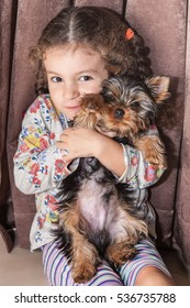 Cute little baby girl cuddle puppy yorkshire terrier at home